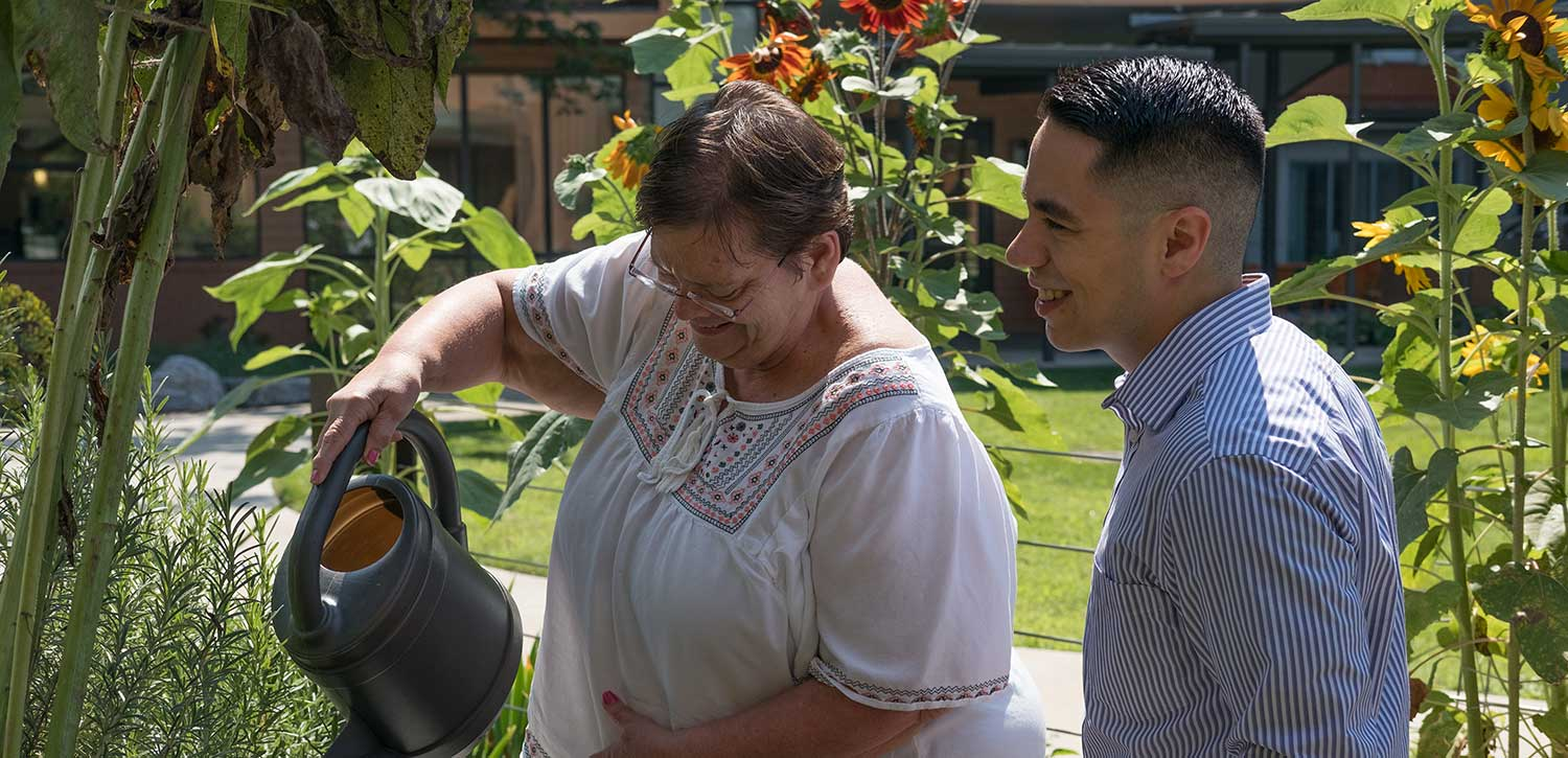 Abe's Garden resident waters flowers with caregiver