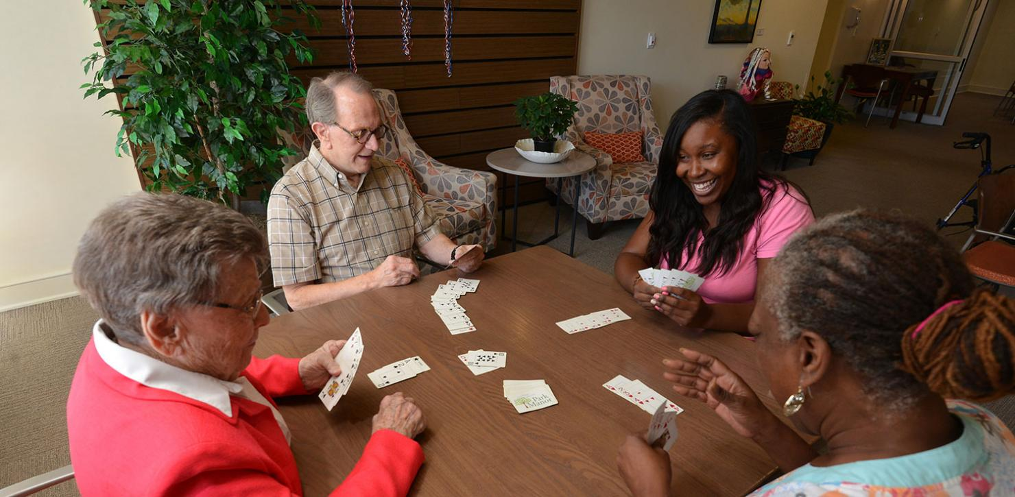 Abe's Garden employees play cards with residents