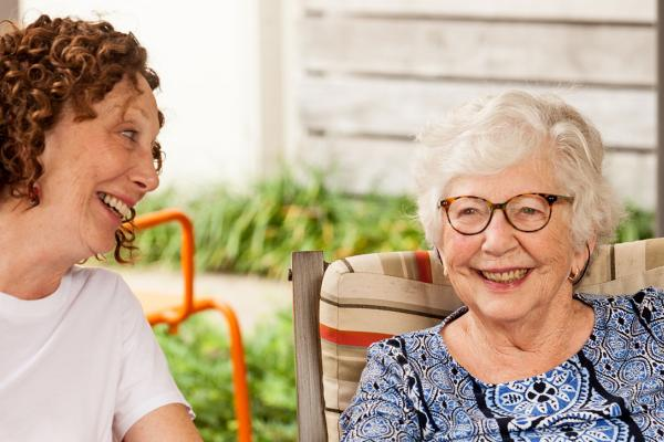 Senior woman and daughter sitting together on a couch and laughing