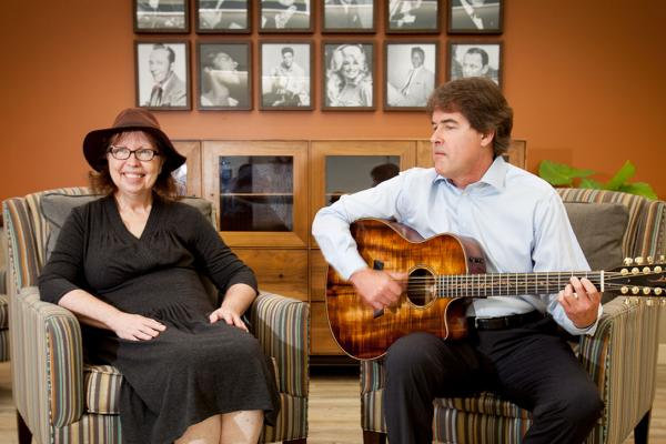 Woman sitting next to a man who is playing guitar